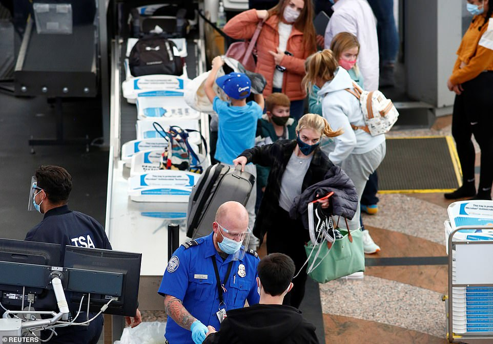DENVER: Travelers wearing protective face masks go through security before boarding a flight at the airport on Tuesday