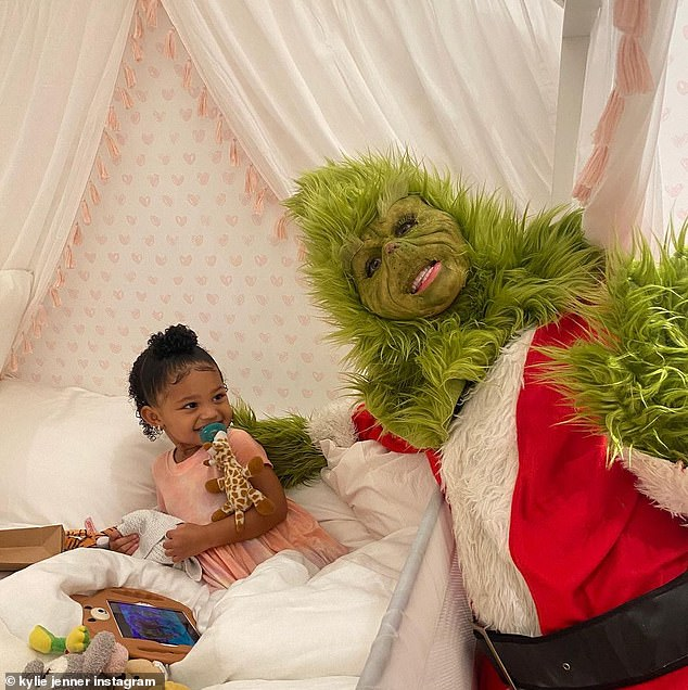 Green is good on her: Stormi seemed to be delighted by the Grinch in a Santa suit