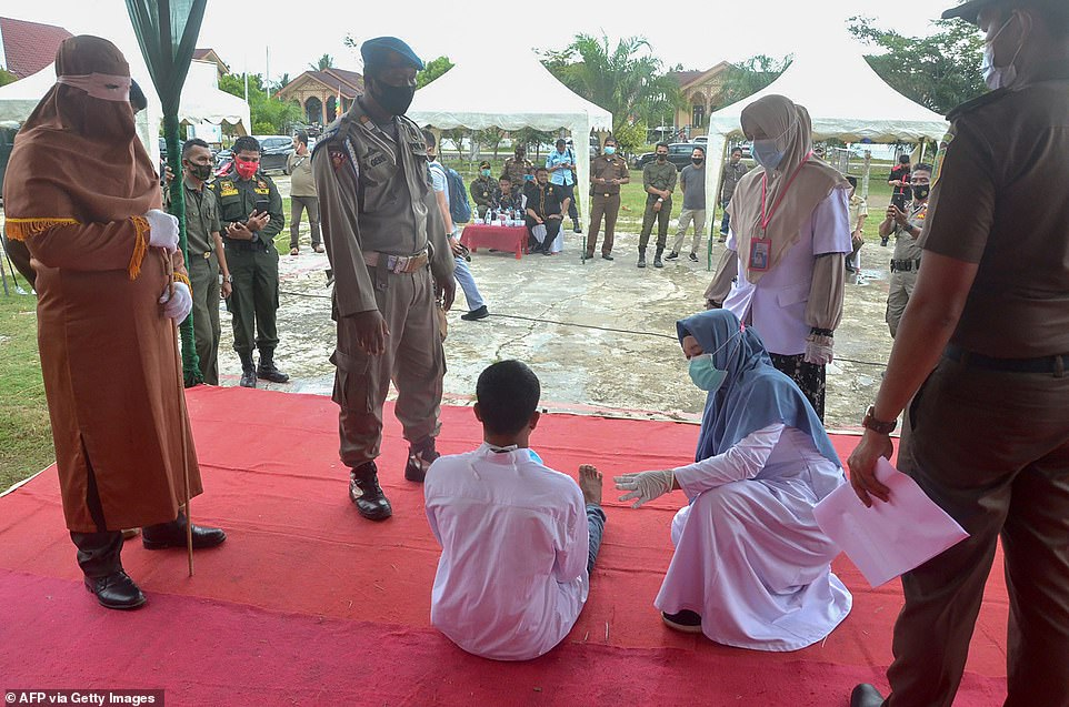 The 19-year-old man is pictured sitting on the floor after he collapsed in pain while being publicly flogged by a member of Aceh's sharia police