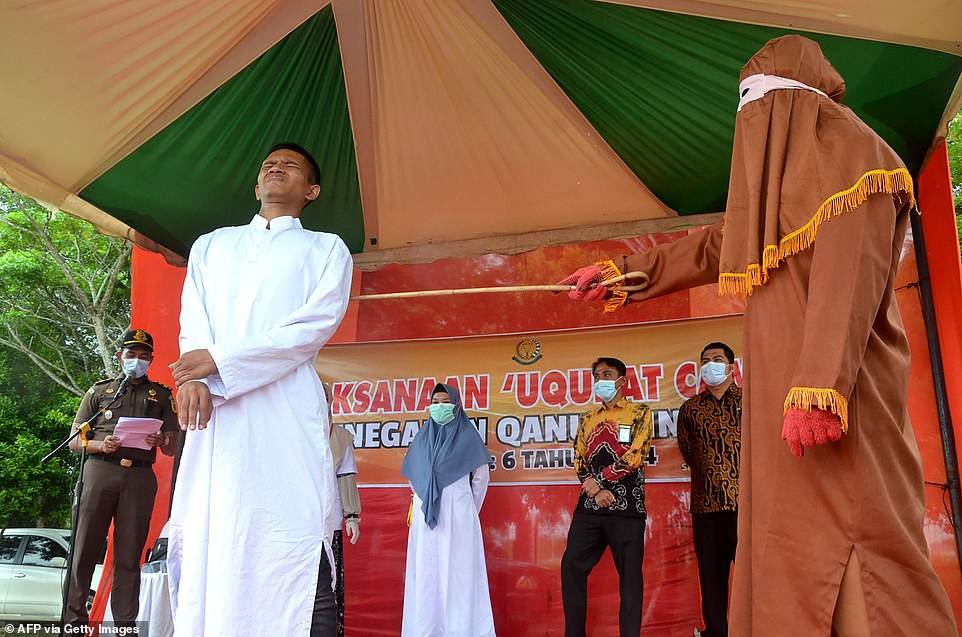 The man winces as he is lashed by a sharia officer for raping a minor in Indonesia's ultra-conservative Aceh province