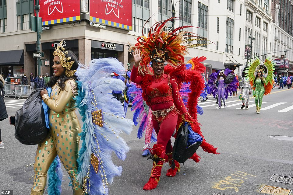 Performers in huge headdresses and brightly colored outfits walk off the set after filming the 2020 parade Wednesday