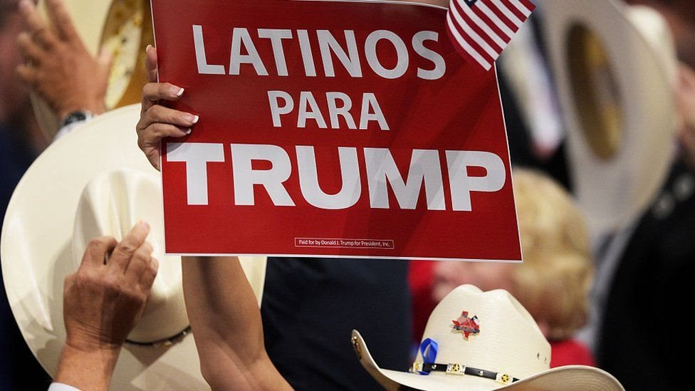 A woman holds up a sign that says Latinos for Trump.