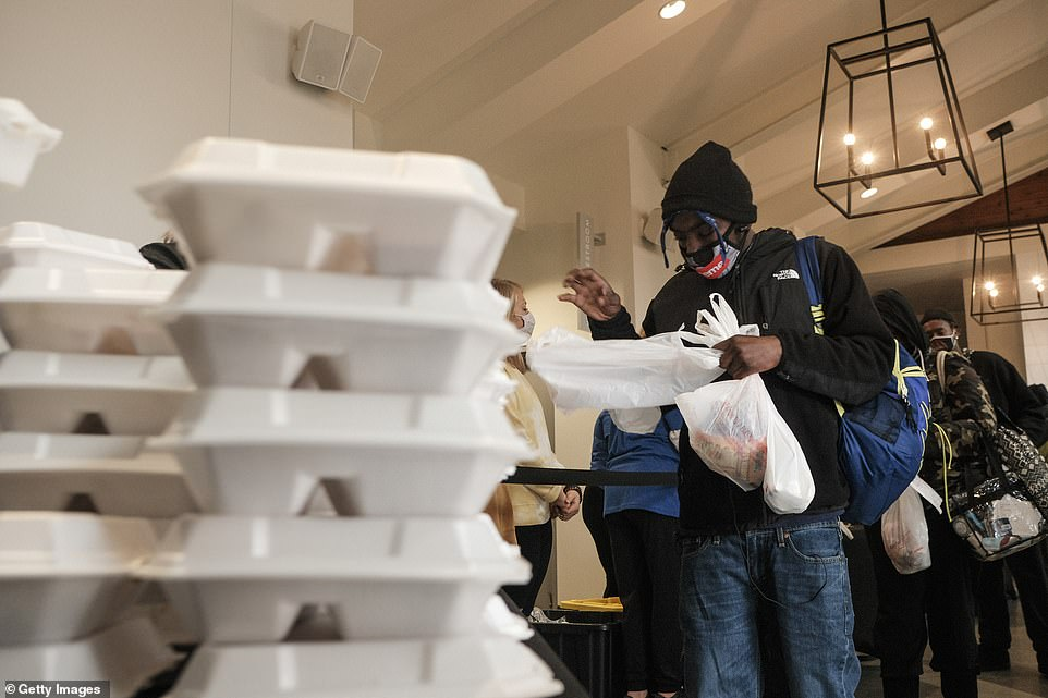 Columbus, Ohio: Several residents are seen getting food and other items during the event on Thursday. Franklin County, where Columbus is located, is one of 4 counties in Ohio that are currently 'purple' the highest ranking color code on the scale measuring the number of Covid cases and risk of transmission
