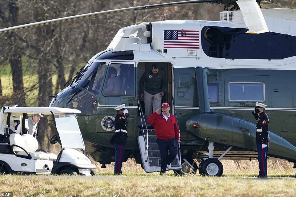 Trump salutedtwo Marines in dress uniforms as he climbed from Marine One, wearing his red golf jacket and red 'Make America Great Again' cap with the number 45 embroidered on the side