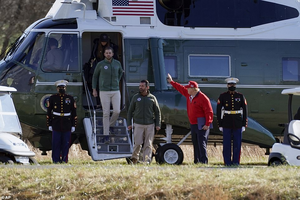 Trump is seen here waving to fans as he got off Marine one with his sons Eric and Don Jr.