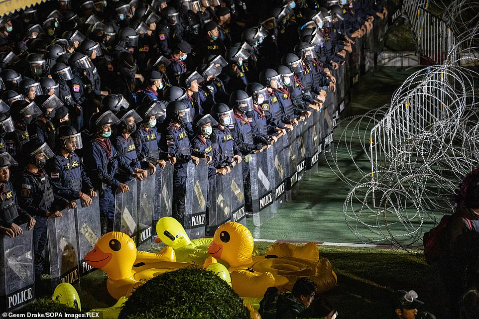 Riot police stand guard behind barbed wires and inflatable yellow ducks during an anti-government demonstration in the Thai capital
