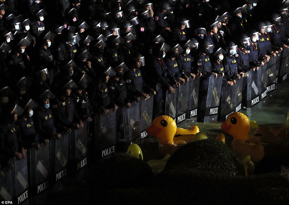 Hundreds of heavily-armoured officers stand guard outside the royal barracks as inflatable ducks are thrown at their feet