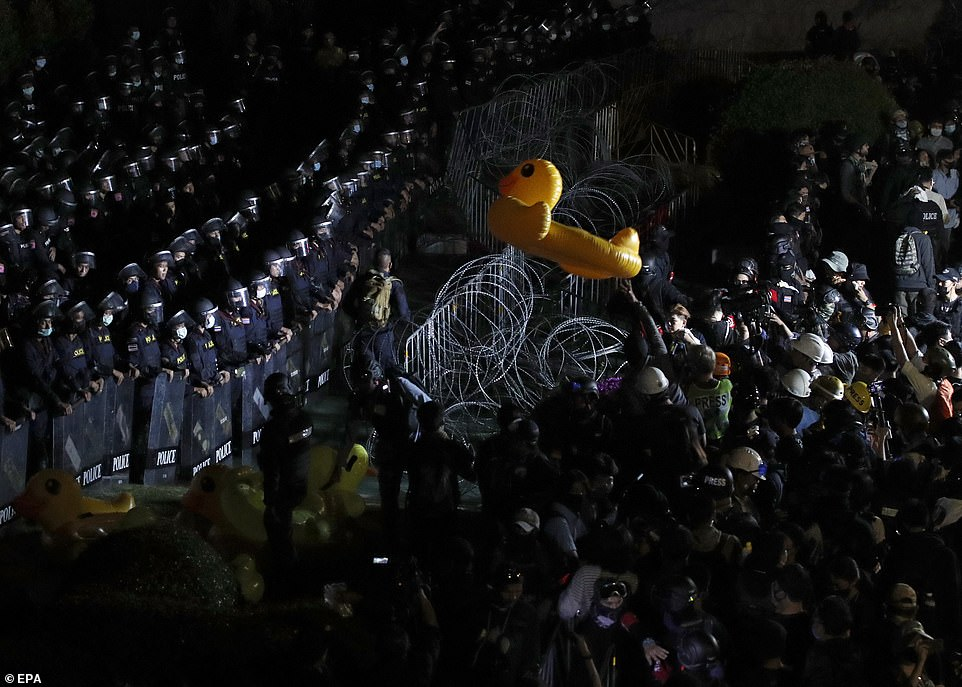 A rubber duck is hurled over the barbed wire towards police officers