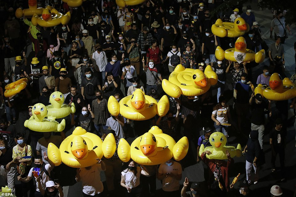 Anti-government protesters march with inflatable rubber ducks during a street protest calling for a political and monarchy reform