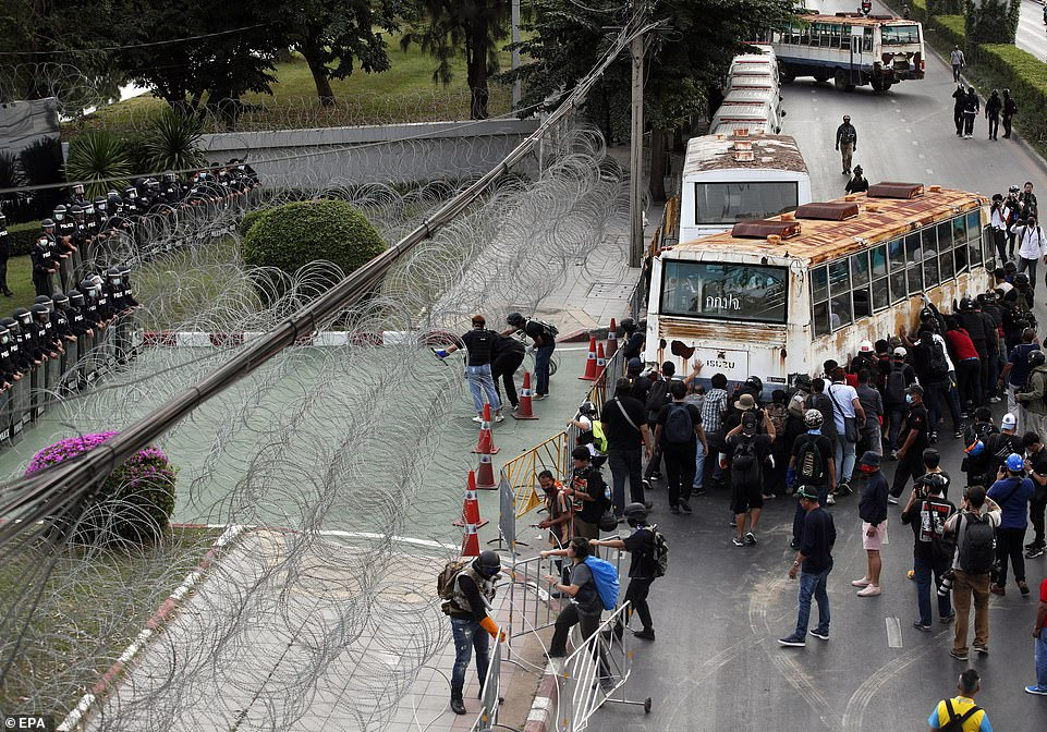 Anti-government protesters remove a bus and barbed wire next to a line of anti-riot police officers during a street protest calling for a political and monarchy reform at the 11th Infantry Regiment, the headquarters of the King's Guard regiment in Bangkok
