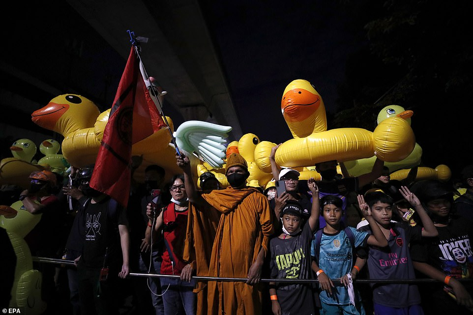 A Thai Buddhist monk (C) joins anti-government protesters marching with inflatable rubber ducks during a street protest calling for a political and monarchy reform