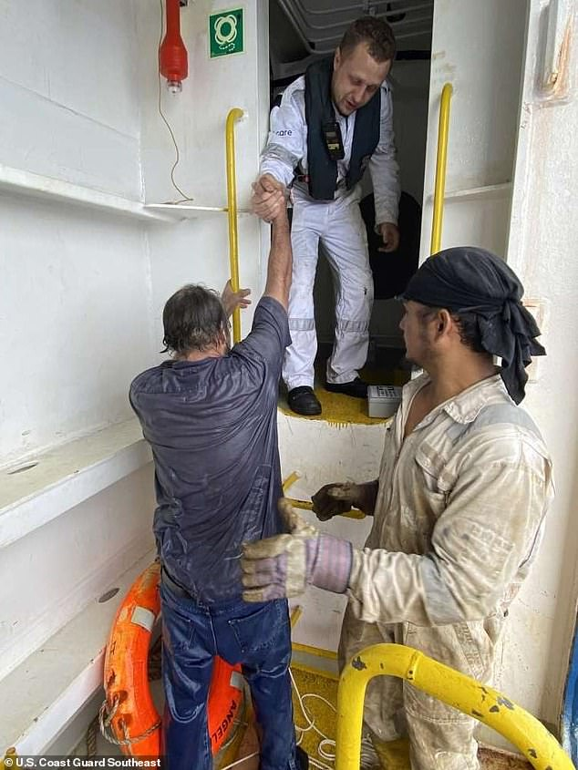 Bee is given a helping hand moments after climbing up the steps of his rescue ship