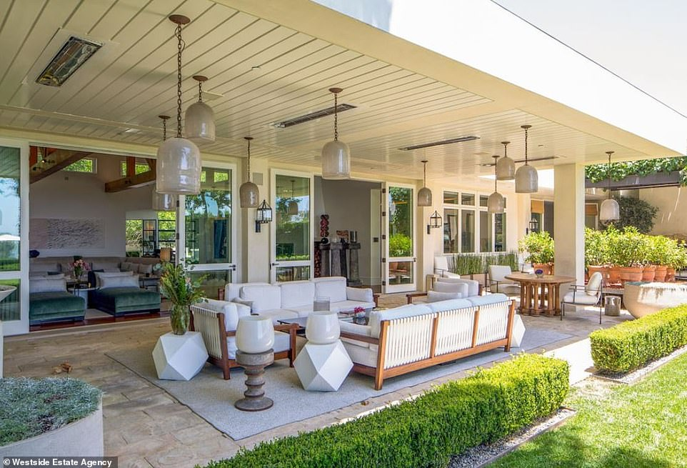 So many incredible places to unwind: The back patio has an outdoor living room and a mini seating area with glass pendant lights and wood ceilings