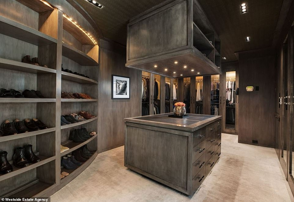 Clothes minded: The walk in closet is as big as most bedrooms in Los Angeles if not bigger. The style is decidedly male with brown/beige wood shelves and walls as well as a golden beige carpet
