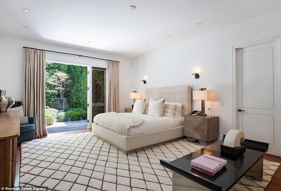 For the guests: One of the four bedrooms is this sweet guest room with recessed lighting in the ceilings and a door that leads to an outdoor space