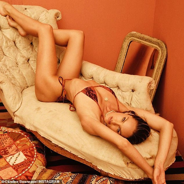 Candice Swanepoel looks amazing as she relaxes on a couch in a python print bikini