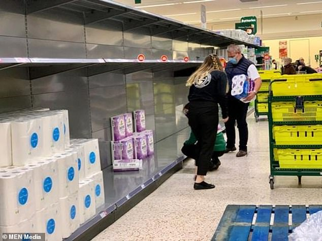 Shelves are emptied of toilet rolls at a Tesco store in Grimsby as sawathes of customers race to bulk-buy household essentials this morning