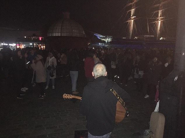 Hundreds of people pack together by the Cutty Sark in London despite strict lockdown rules