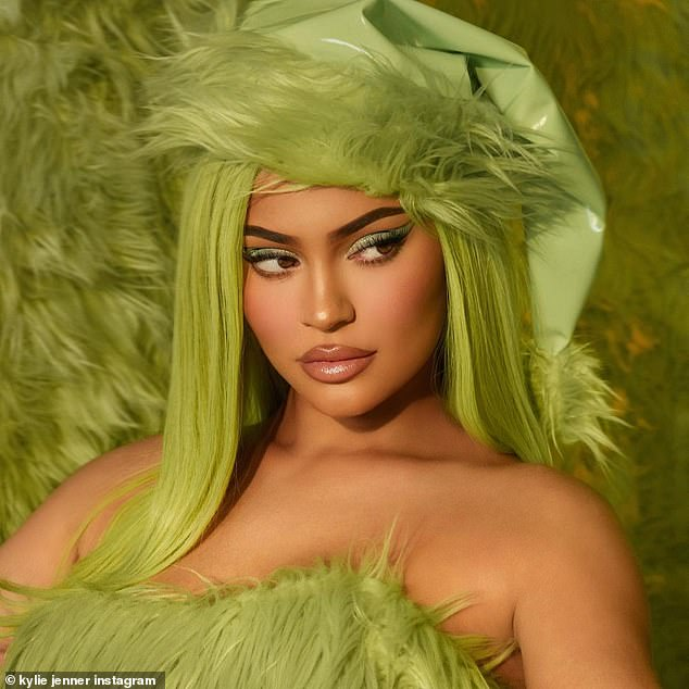 Kylie Jenner poses with green hair as she plugs her new Grinch-inspired cosmetics collection