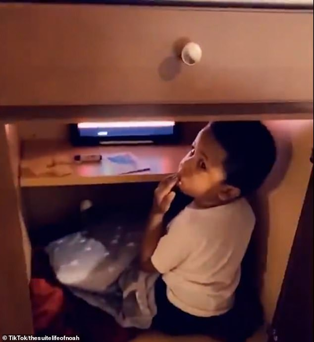 Little man cave! Mother finds her son chilling inside a kitchen cabinet with his iPad and snacks