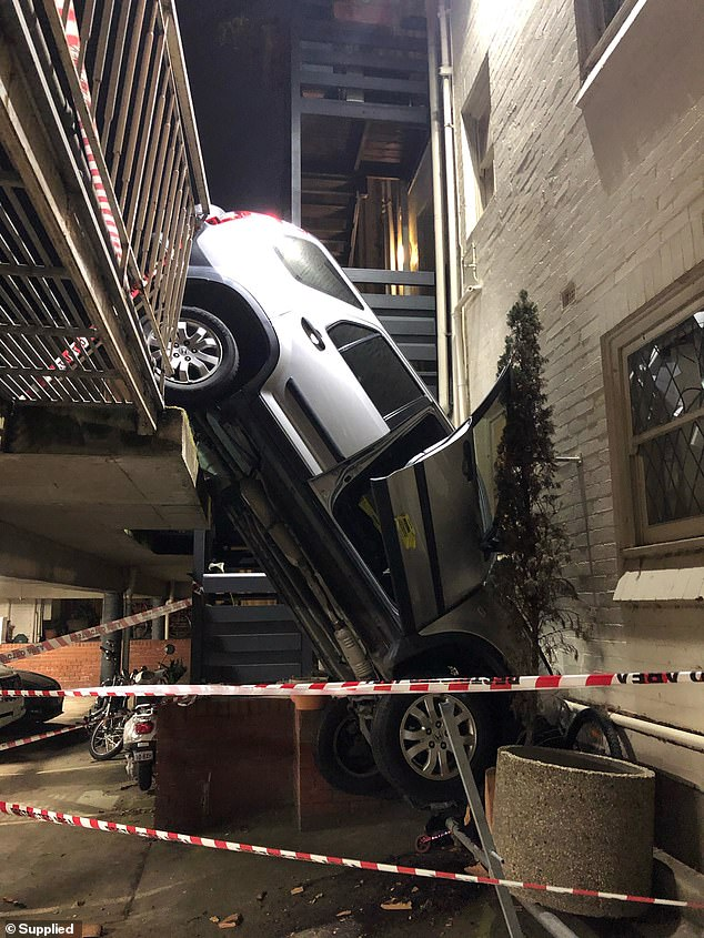 Melbourne: Driver, 46, crashes through safety barrier and gets car stuck between two storeys