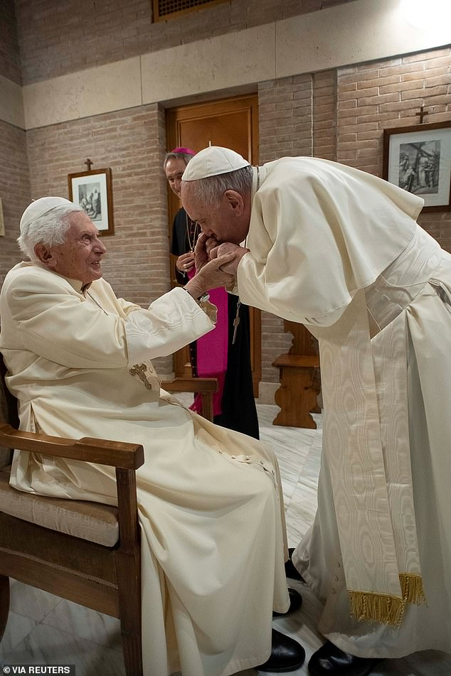 Pope Francis kisses the hand of Benedict XVI