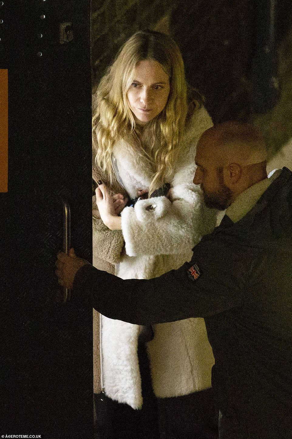Model Poppy Delevingne was seen walking into the restaurant in a white fur coat while clutching a bottle