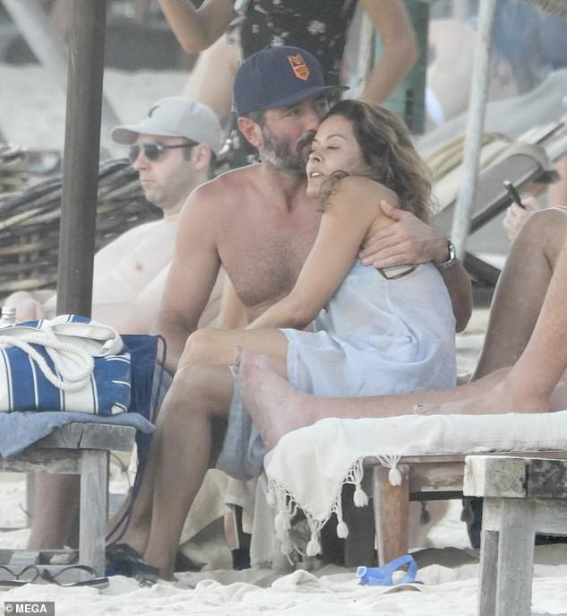 Love: Scott wrapped his arm around his lady love for a quick quiet moment as they relaxed amid a group of friends