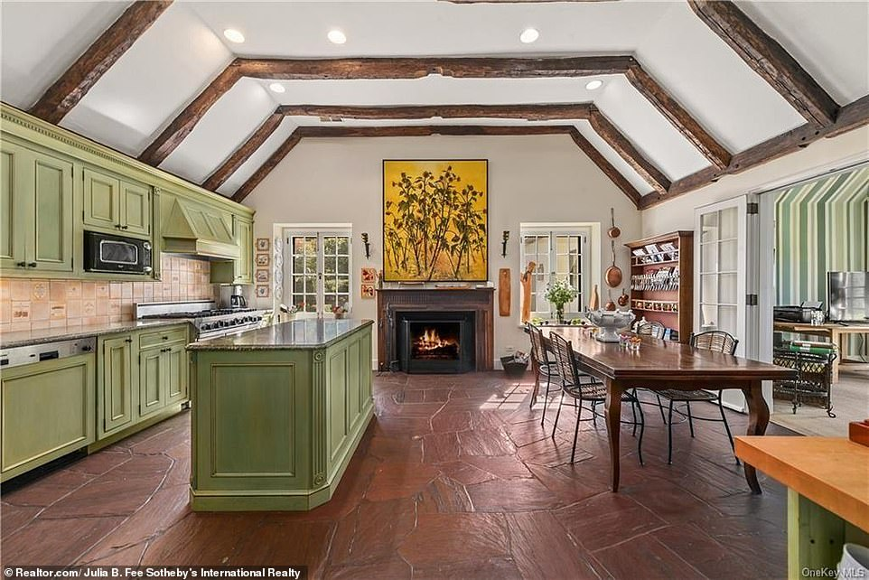 The image above shows the kitchen that has one of thefive wood-burning fireplaces on the property