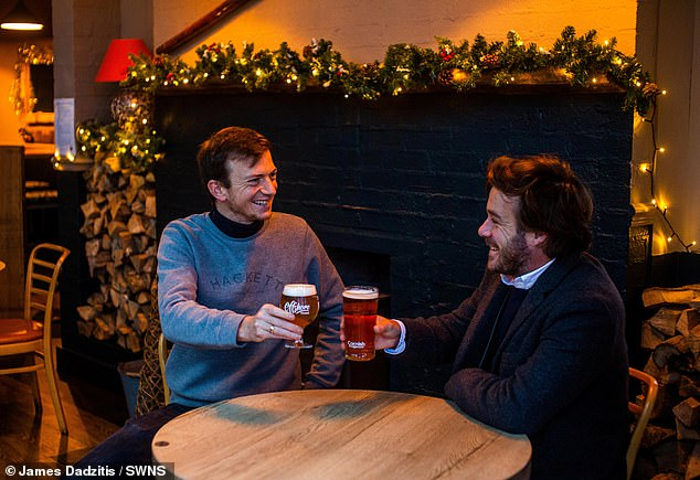 Eager pub-goers were seen returning to watering-holes this morning for a pint in the pub (pictured: Two people enjoy a drink at the Five Degree West in Falmouth, Cornwall