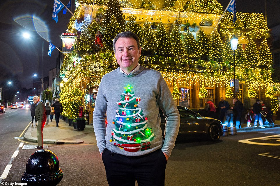 The Churchill Arms' Christmas lights are a West London icon - and manager James Keogh poses outside with a Christmas jumper