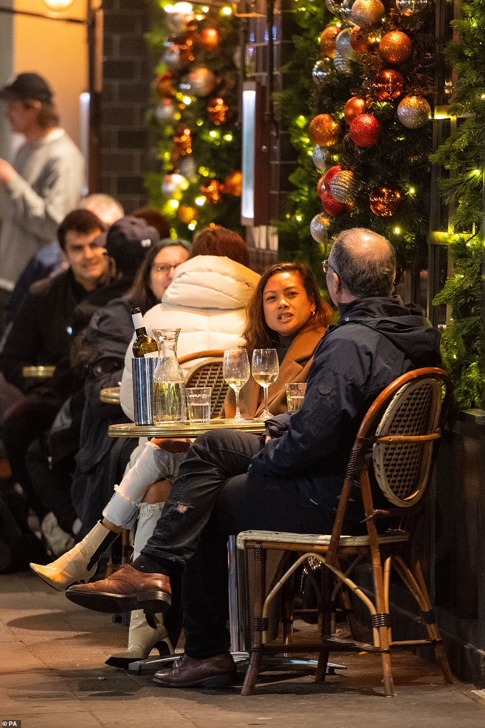People eat and drink outside bars and restaurants in the West End last night following the easing of restrictions in England