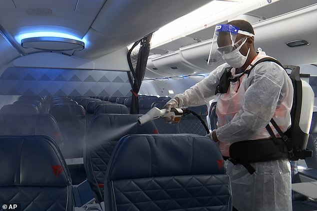 A Delta employee disinfecting a plane after use. Despite the airline's security measures, the CDC is urging people not to travel to visit family over the holidays to avoid spreading the virus