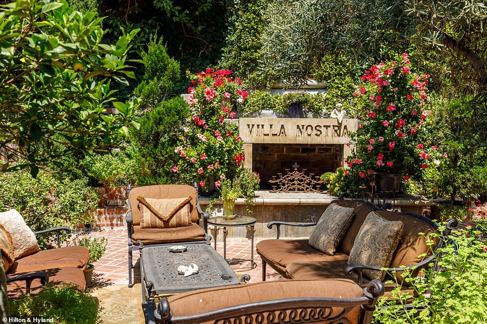 An outdoor seating area next to a large, stone fireplace provides a setting for cozy evenings