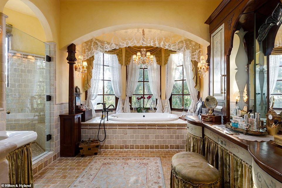 A large ensuite has double sinks and mirrors on a dark wood vanity, with velvet drapes providing coverage to personal items.Stone work lines the glass shower, and tub tucked under a window