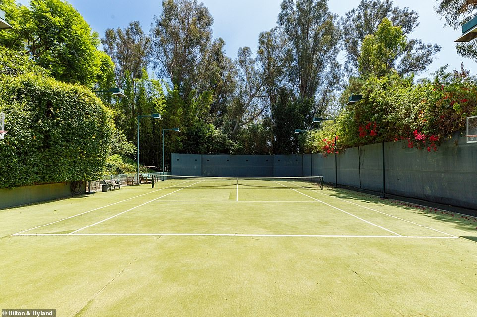 The tennis court surrounded by trees comes with floodlights and a basketball