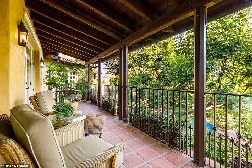 A large balcony with red stone flooring and wrought iron railing has views of the backyard and pool