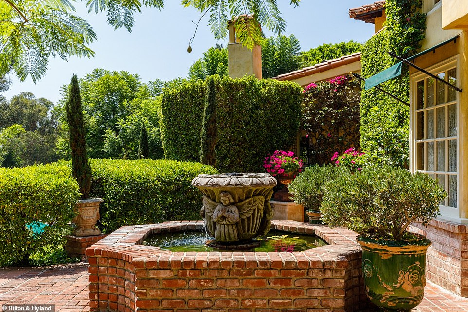 Outside, short shrubs line the walkways with brick detailing in the driveway and paths, and as well stairs leading from the indoor living space outside
