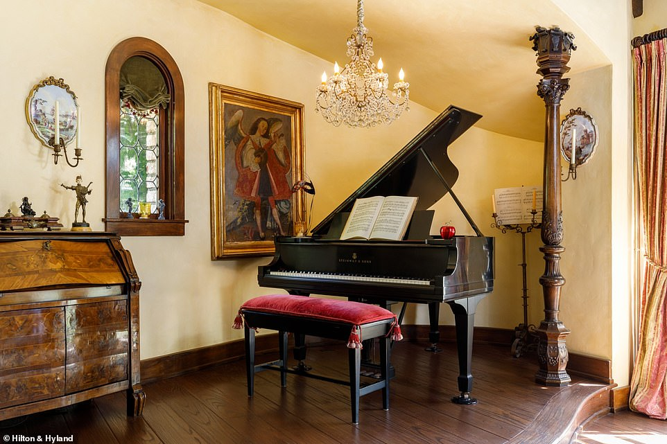 A Steinway & Sons grand piano sits under a chandelier in the corner of one of the rooms