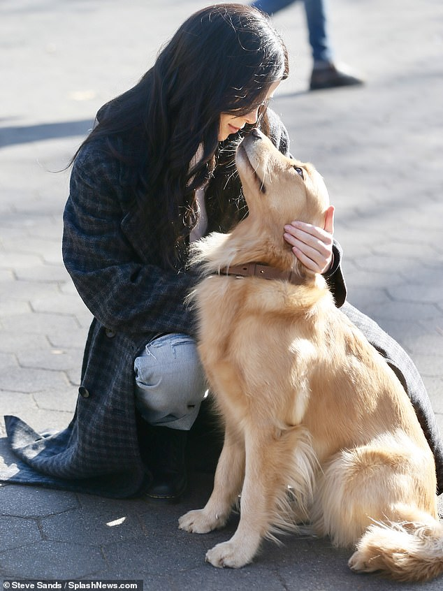 So sweet: She could be spotted dropping to a squat to shower some affection on her canine co-star, who appeared to be a golden retriever