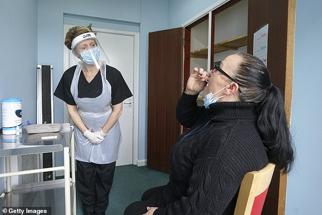 Sarah Hatchett, Head of Care at King Charles Court nursing home, Falmouth, oversees the demo of a rapid Covid-19 test on Manager Melissa Jones during pilot programme in November