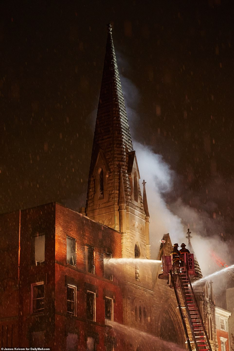 The roof of the church has been destroyed, but firefighters are trying to save its steeple