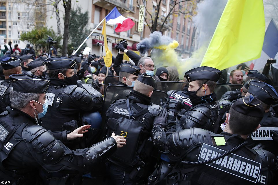 Protesters were blocked by riot police officers during the demonstration this afternoon in Paris as yellow flares were set off