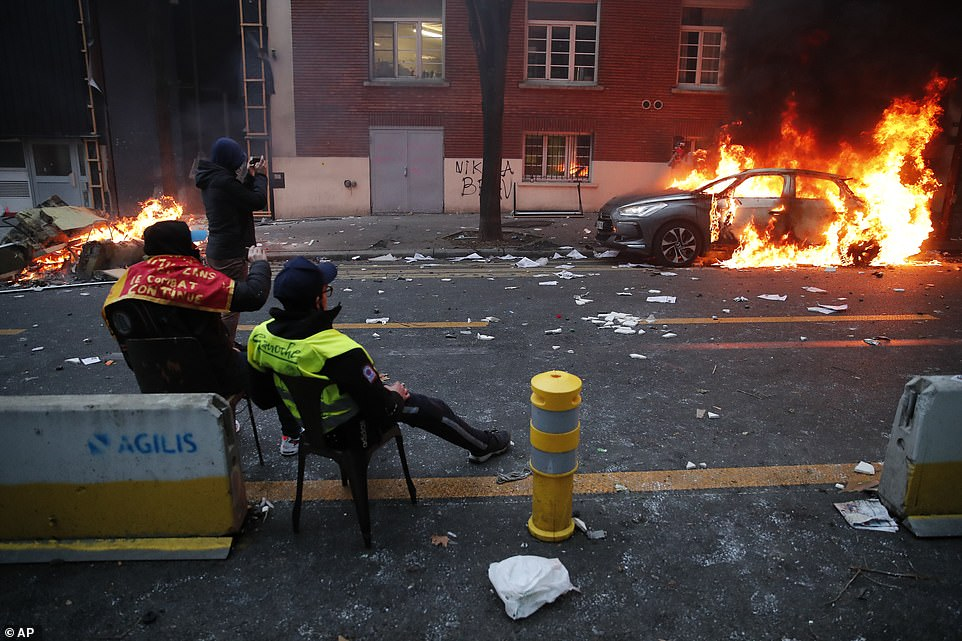 Some demonstrators sat on chairs watching a car which had been set alight during the clashes in Paris