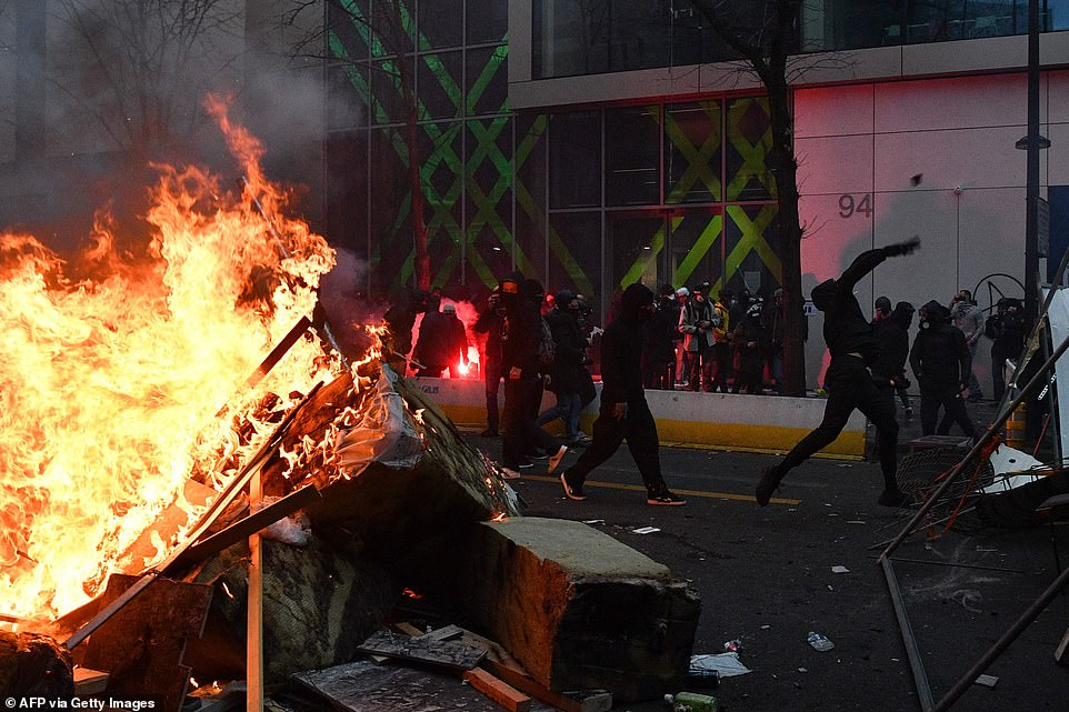 Protestors were seen throwing items in the street while standing beside a burning barricade in Paris