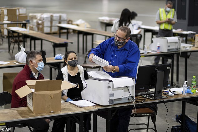 Workers scan ballots in Atlanta, Georgia, during the state's recount last month. The Trump campaign has filed 46 lawsuits since Biden was named President-elect but none of them have made headway