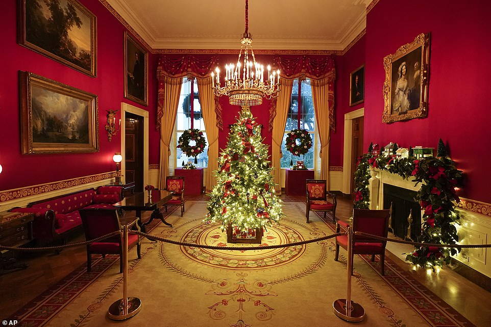 Decorations in the red room are dedicated to first responders, front line workers and essential employees like grocery store workers.The village scene on the fireplace mantel includes a hospital and grocery store