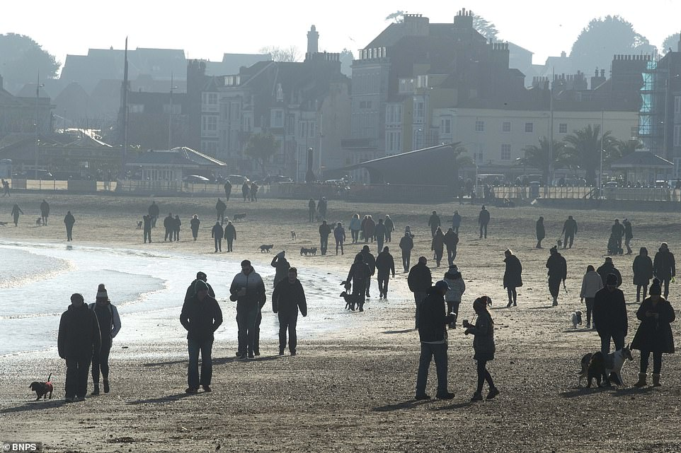 While temperatures have dropped, families and locals still braved the cold to walk along the beach in Weymouth, Dorset today