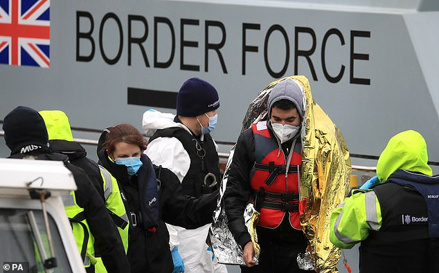 A man is helped by a Border Force officer as a group of people thought to be migrants are brought in to Dover last month