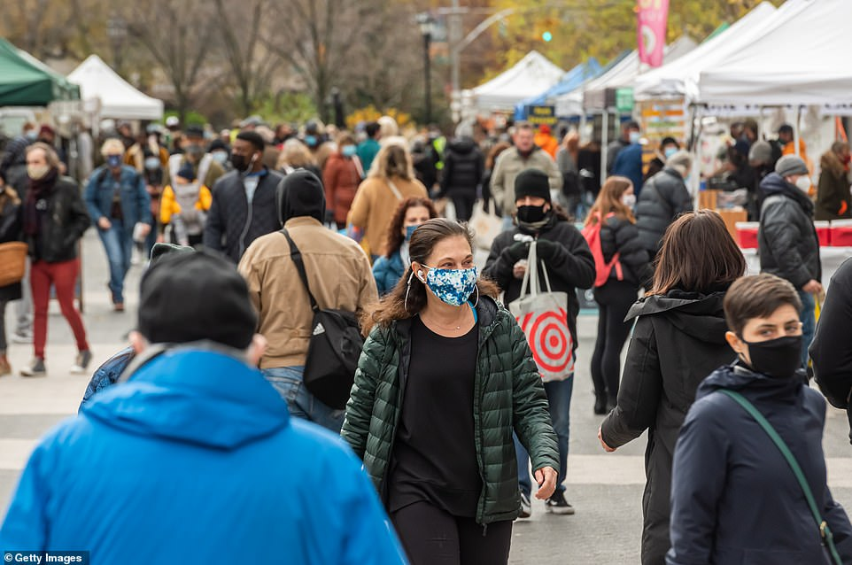 People wear protective face masks while shopping at the Union Square Greenmarket on Friday in New York City